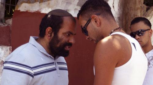 شاب فلسطيني ومستوطن اسرائيلي امام أحد المنازل المحتلة في القدس الشرقية (عمار عوض - رويترز)
